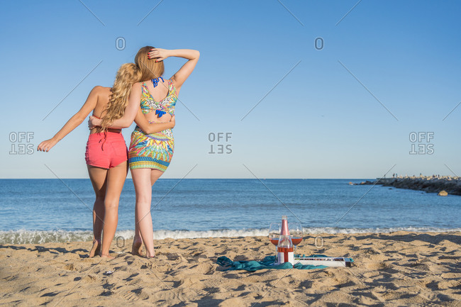 Back view of anonymous lovers women in stylish clothes embracing each other and admiring sea while standing on sandy beach against cloudless sky during picnic