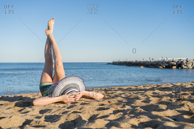 A woman in a beach hat lying with her feet on the beach sand looking at the horizon