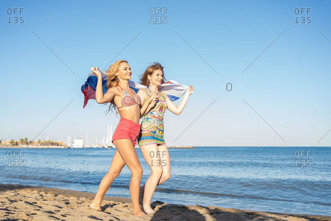 Two young women walk happily along the seashore wrapped in the Russian flag