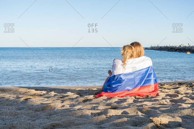Rear view of two young women hugging each other sitting on the sand of the beach looking at the horizon wrapped in the Russian flag