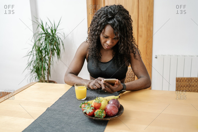 Young adult african american woman in sports clothing at home, while consulting her smartwatch