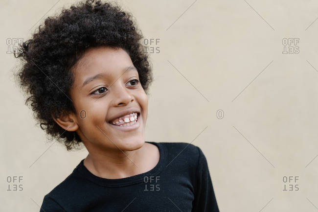 Portrait of smiling afro boy in black shirt on beige background