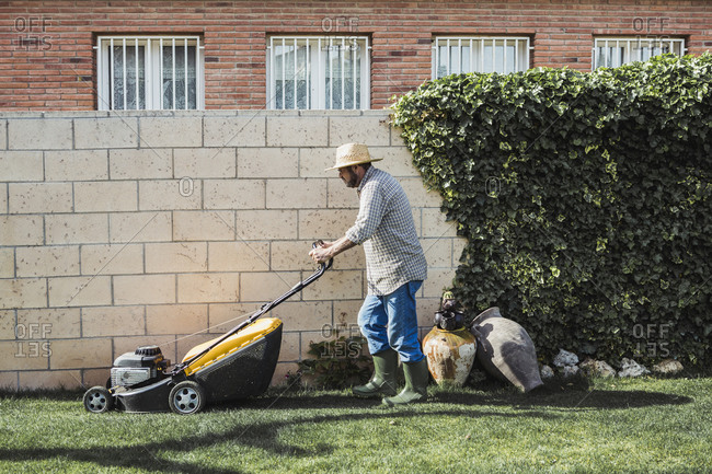 Senior man mowing the lawn at home