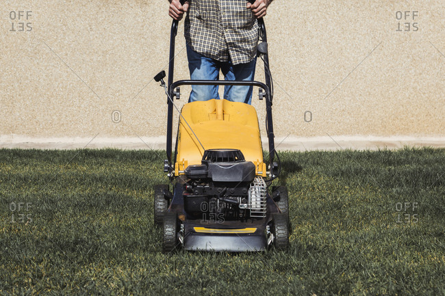 Detail of a man mowing the lawn with a lawn mower in the garden