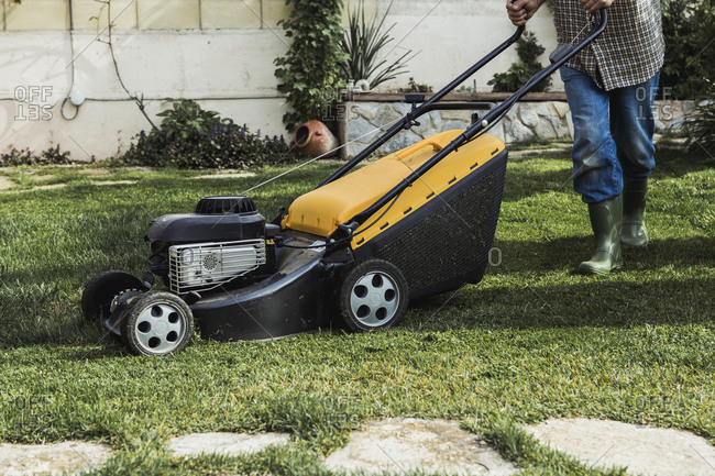 Man mowing the lawn in his garden
