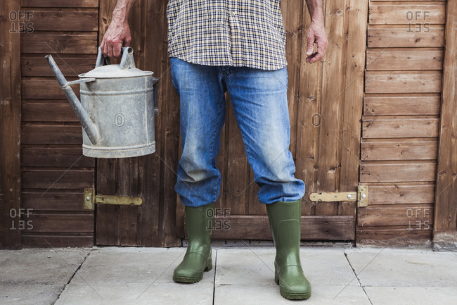 Man in blue jeans and green boots holding an old watering can