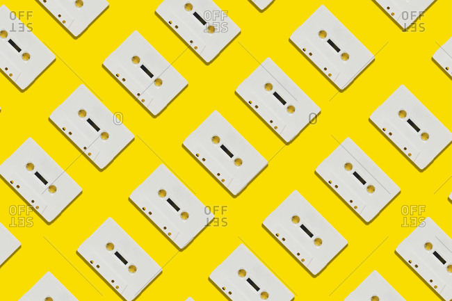 Row of white cassettes on yellow background