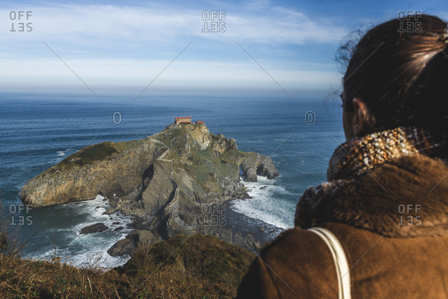 Brunette girl looking at the chapel of San Juan de Gaztelugatxe (Basque Country, Spain)