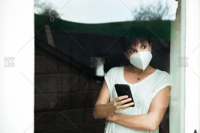 Portrait of a concerned woman with a white mask at home looking outside while she holds her smartphone through a glass door