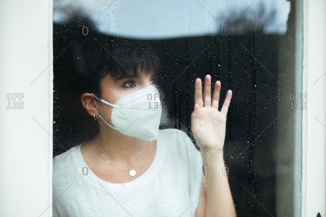 Portrait of a hopeful and nostalgic woman with a white mask at home looking up through a glass door with rain drops