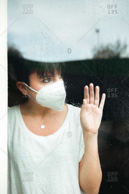 Portrait of a hopeful and nostalgic woman with a white mask at home looking outside with a hand over a glass door with rain drops