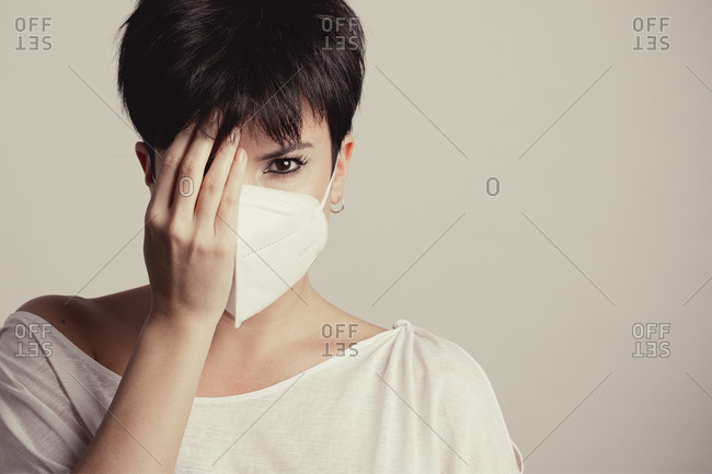 Portrait of a serious woman with a white mask in studio looking at camera while she covers half of her face with her hand