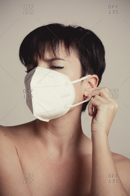 Portrait of an uncomfortable woman in pain removing a white mask in studio