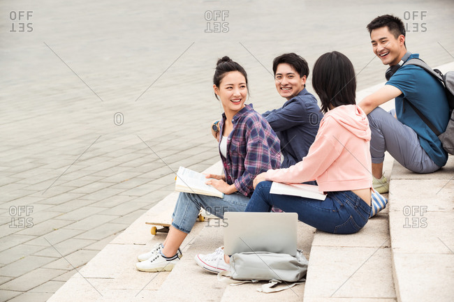 Outdoor college students sat on the steps to chat