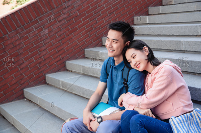 Sweet college students sat down on the stairs