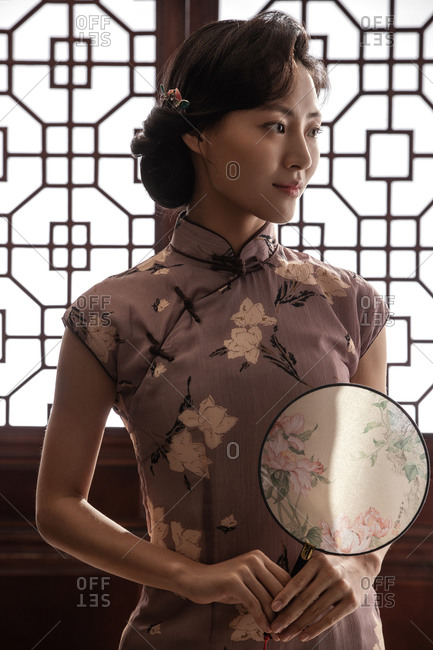 Oriental women wear qipao with a fan