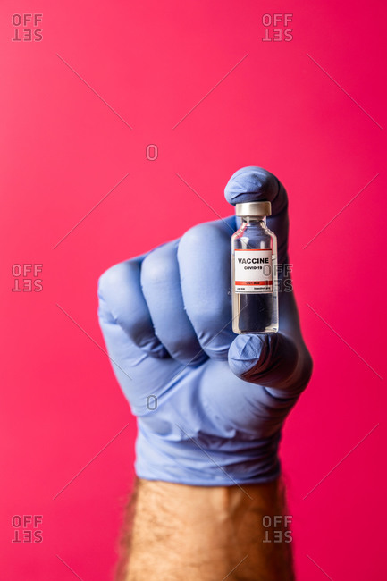 Unrecognizable doctor's hand showing the covid-19 vaccine on pink background