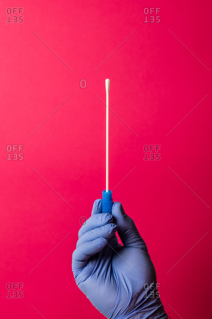 Unrecognizable doctor's hand showing swab test for covid-19 on pink background