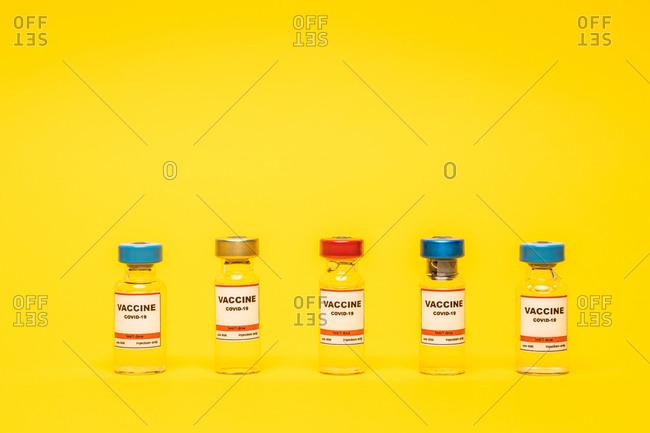 Front view of coronavirus vaccine bottles over yellow background.