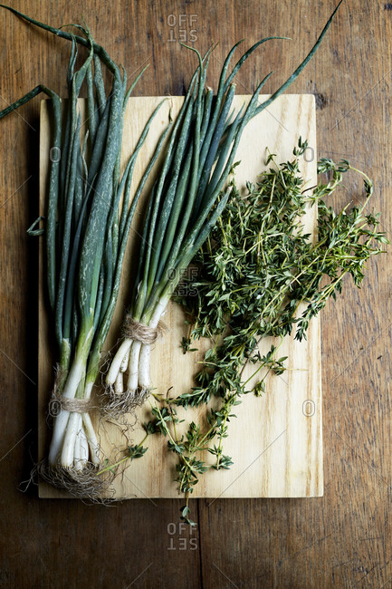 Fresh spring onions and thyme on a wooden kitchen counter,