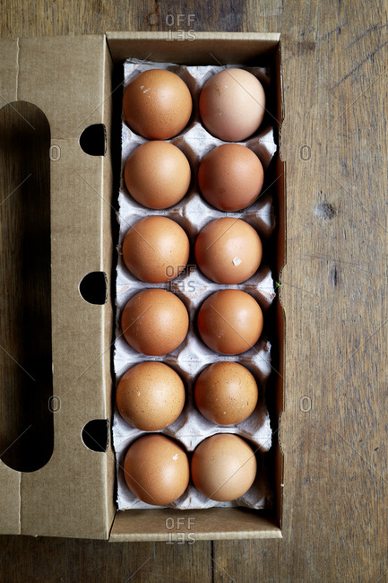 Whole, raw eggs in an egg tray on a wooden kitchen table,
