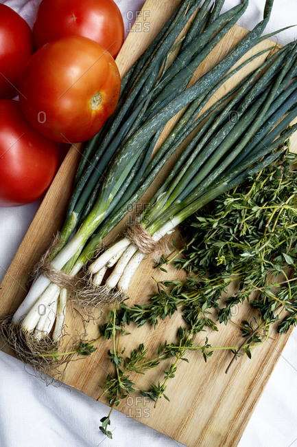 Fresh produce, spring onions, thyme and tomatoes laid out on a kitchen counter,