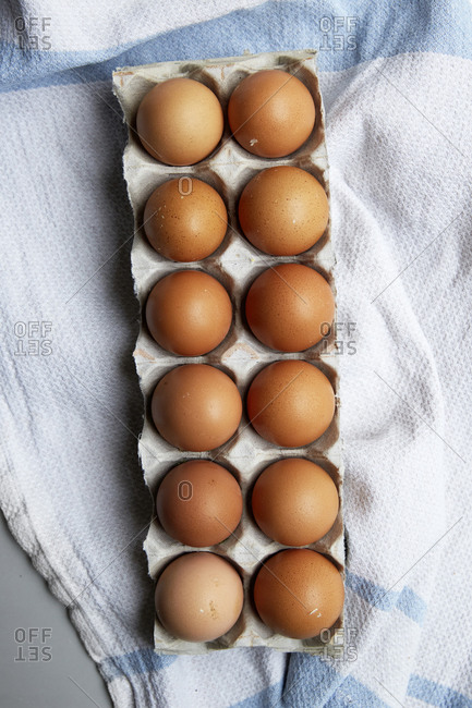 Whole, raw eggs in an egg tray on a kitchen counter with a kitchen towel,