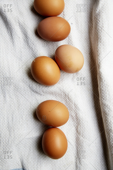 Whole raw eggs laid out on a kitchen cloth shot from above,