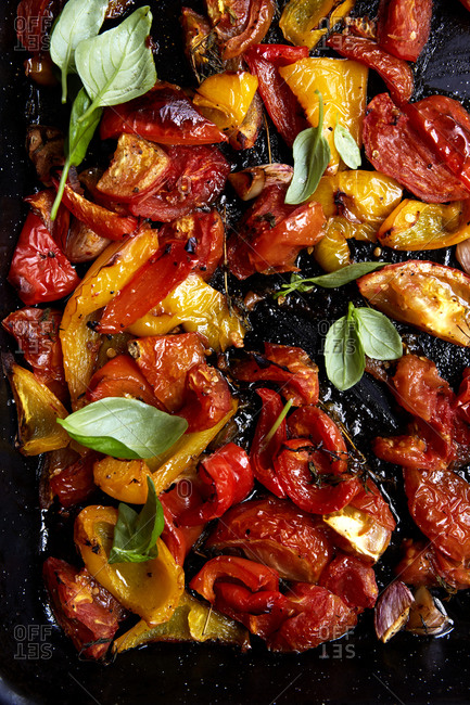 Roasted red and yellow peppers and tomatoes with garlic and thyme in a roasting tray straight from the oven,