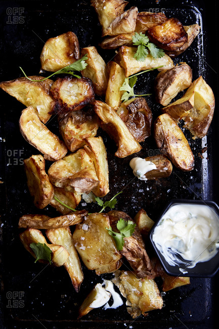 Crispy roasted potatoes with fresh herbs and dipping sauce on a baking tray,