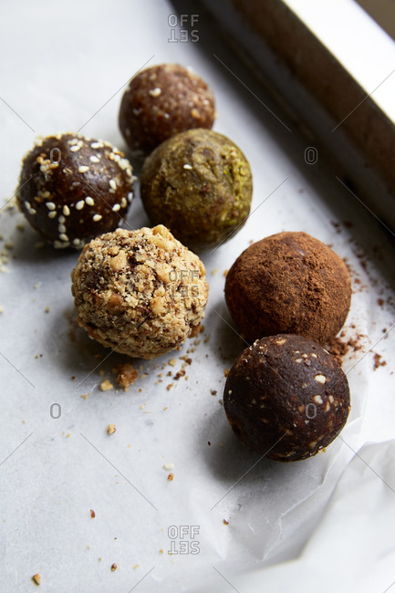 Different types of date balls laid out on wax paper in a baking tin,