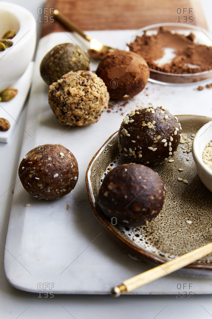 Date balls on a marble plate with cacao powder, sesame seeds and pistachios on the side on a white countertop,