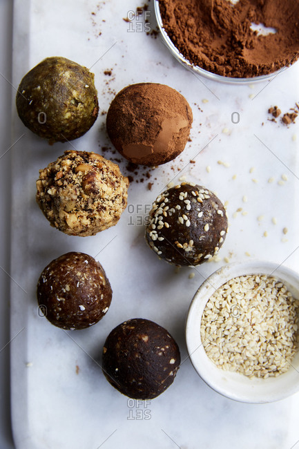Date balls on a marble plate with cacao powder and sesame seeds on the side on a white countertop,