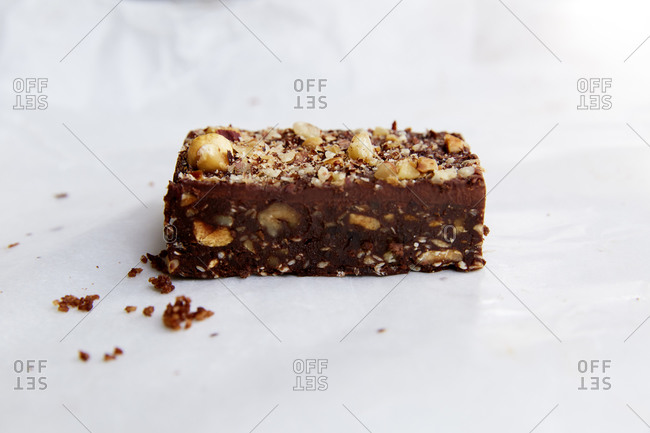 A side view of a decadent brownie with nuts on white,