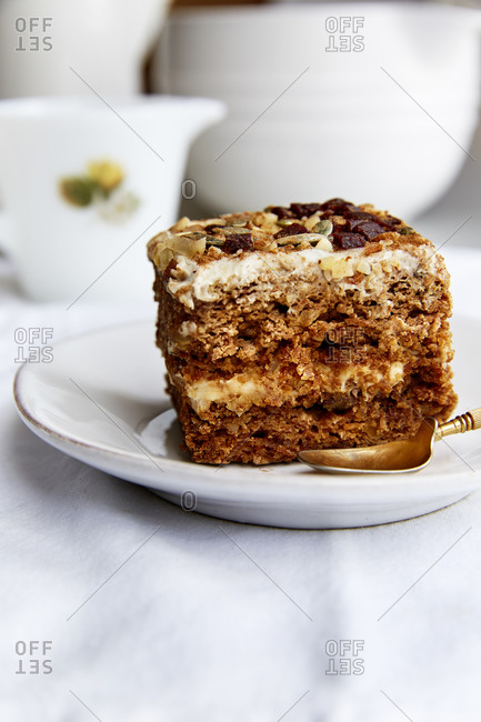 A side view of a slice of carrot cake topped with nuts and seeds in a white linen cloth,