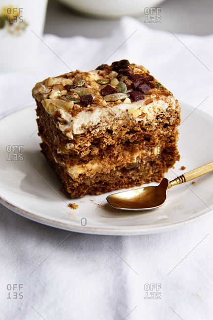 A slice of carrot cake topped with nuts and seeds in a white linen cloth,