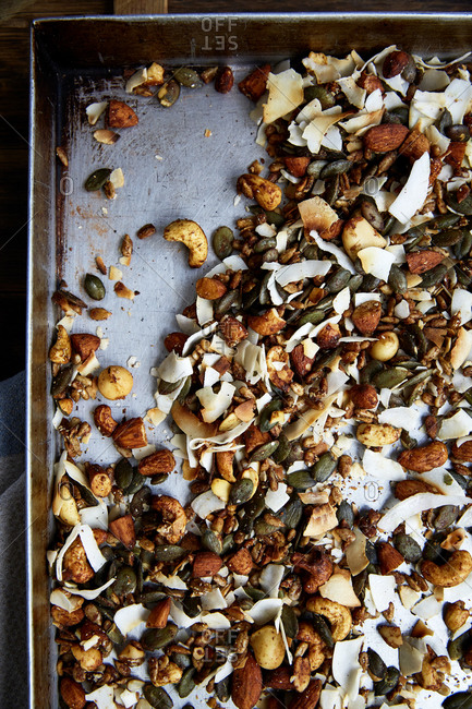 Seed, nut and coconut flake granola in a baking tray straight out of the oven,