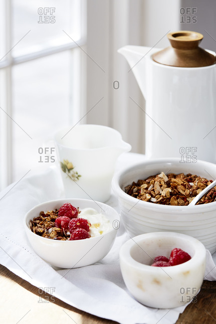 A bowl of yoghurt and granola and honey with fresh raspberries and a pot of tea served,