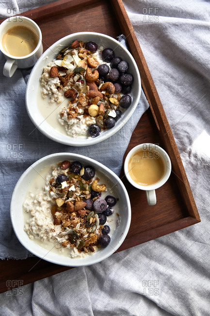 Warm oats and fresh granola topped with blueberries and espresso on a wooden serving tray,