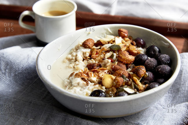 Side view of warm oats bowl and fresh granola topped with blueberries and espresso on a wooden serving tray,