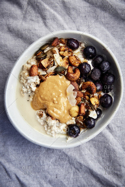 Warm oats bowl topped with fresh granola and blueberries on a linen cloth,
