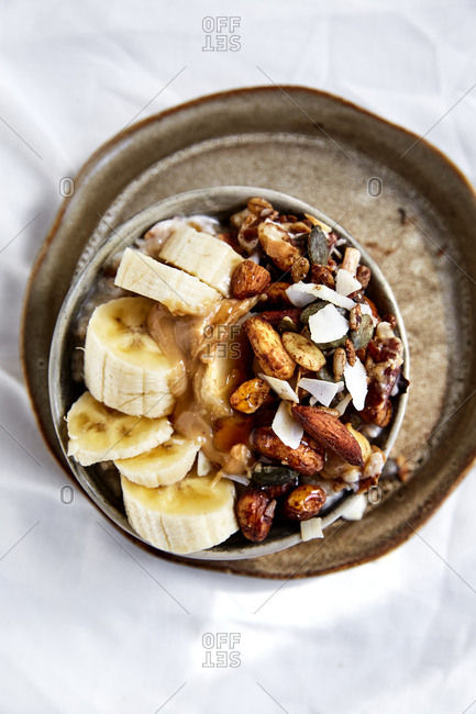 Granola bowl topped with banana, nut butter and honey,