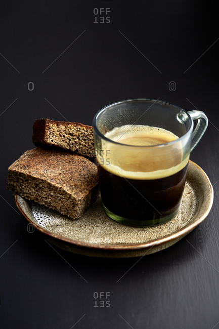 A cup of black coffee with two biscuits on the side on a black table,