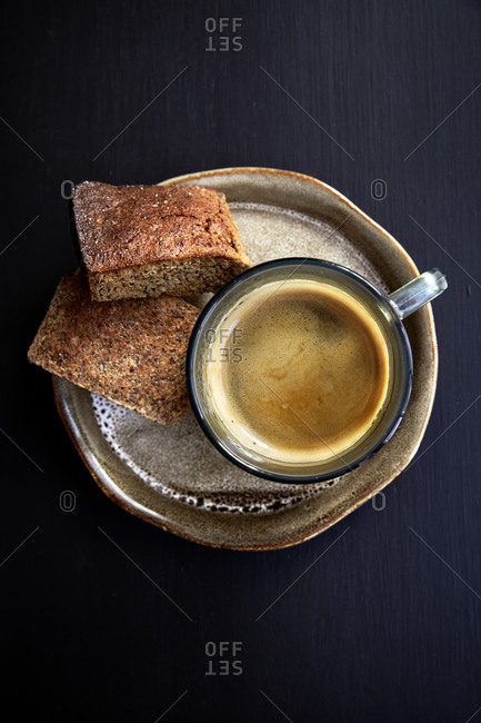 A view from above of a cup of black coffee with two biscuits on the side on a black table,
