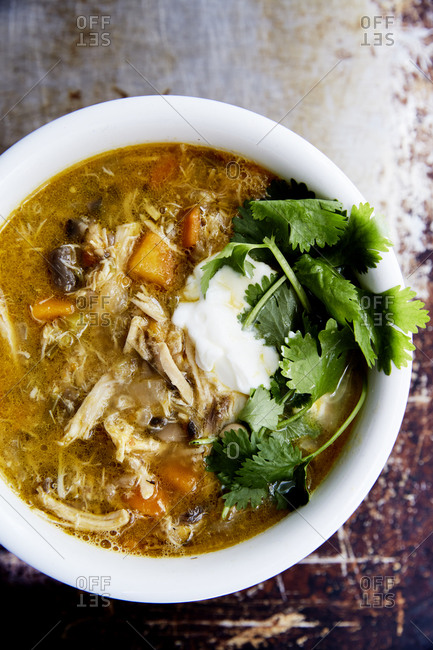 Close up of immune boosting chicken soup with a spoonful of yoghurt and fresh herbs on a rustic background,
