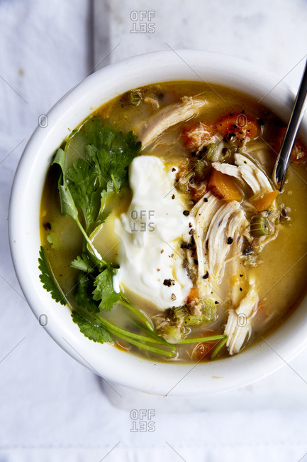 Close up of immune boosting chicken soup with a spoonful of yoghurt and fresh herbs on a light background,