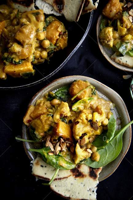 Vegetable and chickpea curry served into plate with the main dish on the side on a dark background,