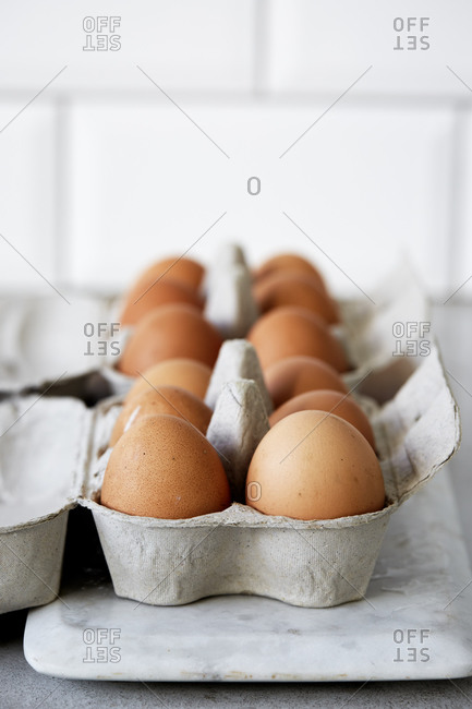 Side view of whole eggs in egg boxes on a kitchen counter,