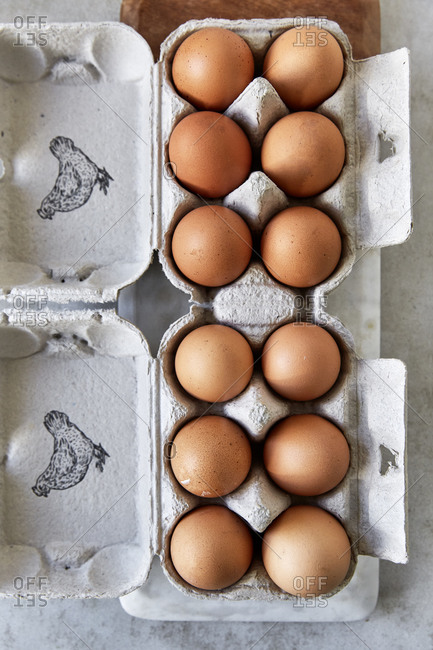 Overhead of eggs in egg boxes on a kitchen counter,