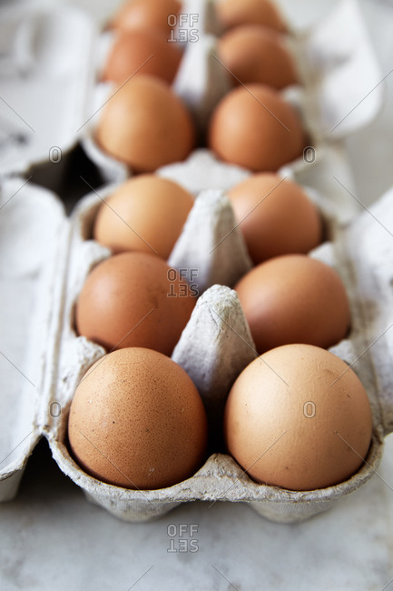 Close up side view of whole eggs in egg boxes on a kitchen counter,